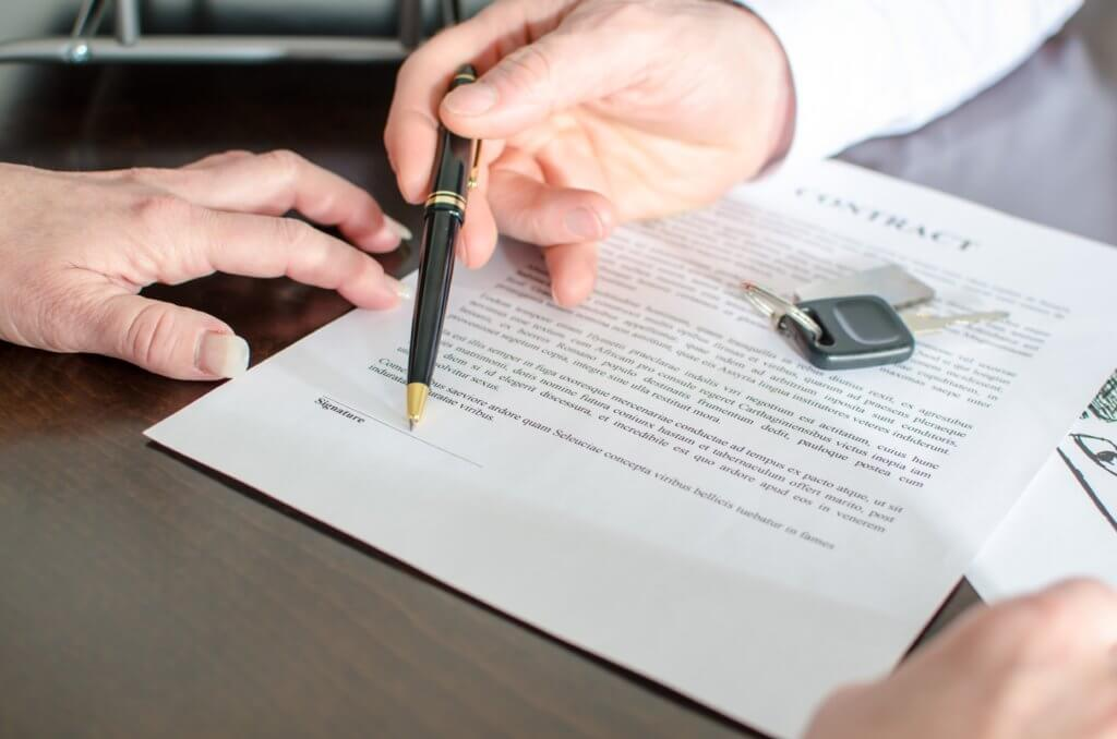 Man handing a pen to a woman to sign a contract, with vehicle keys on the paper