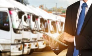 Man in a suit managing a fleet of trucks with a tablet