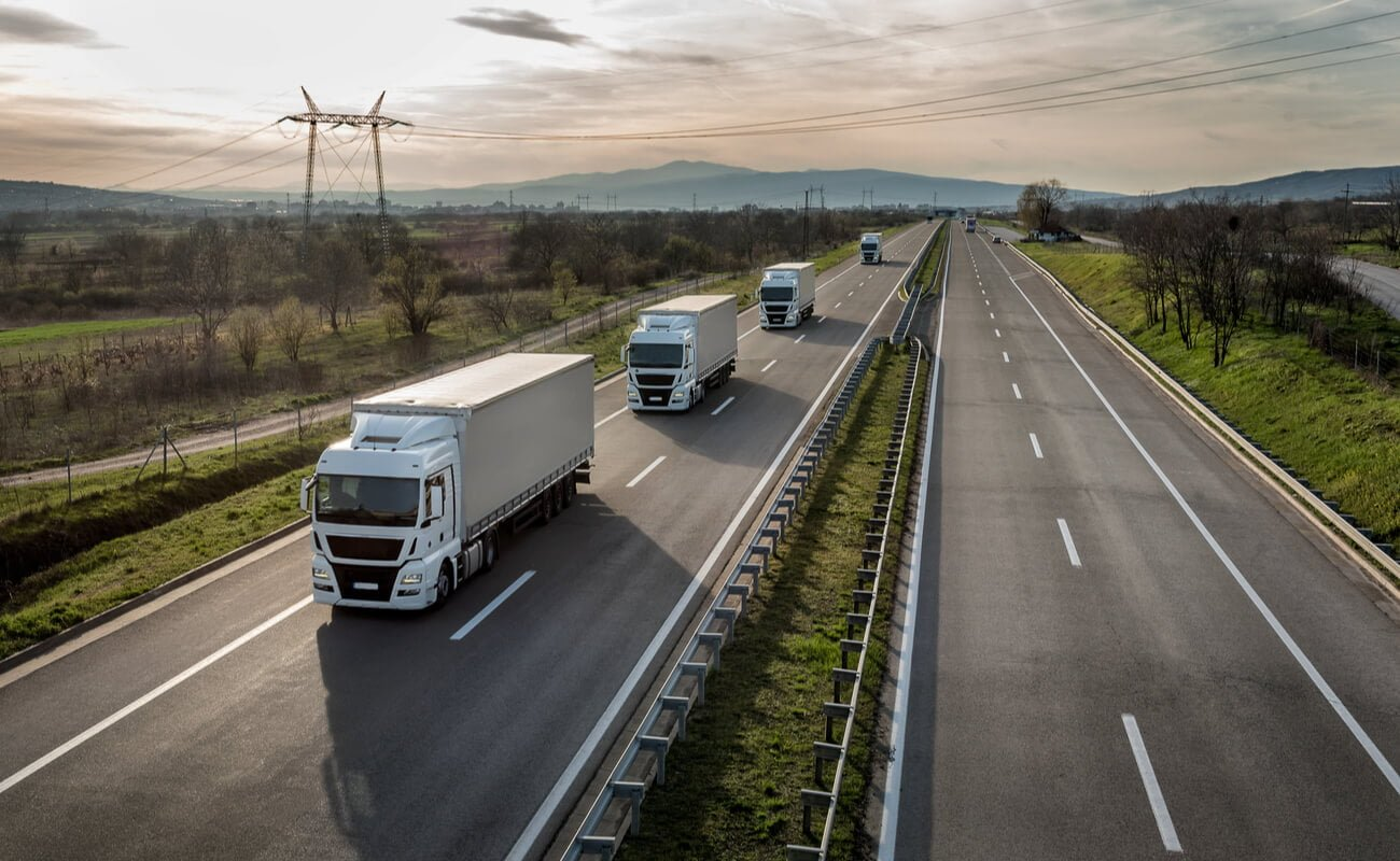 A fleet of trucks driving down a country road