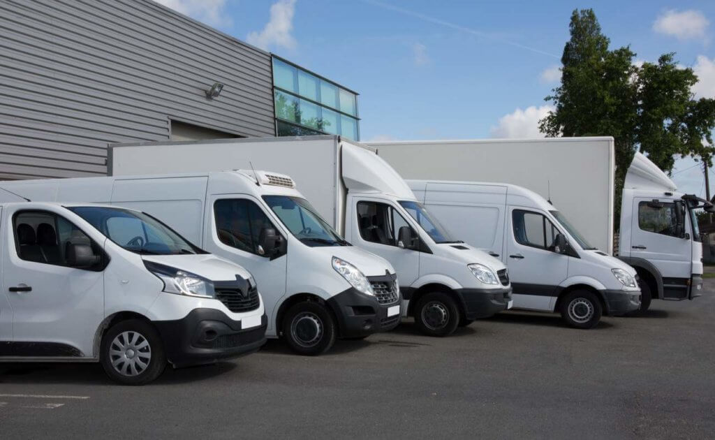 A lineup of different types of commercial vehicles outside a depot