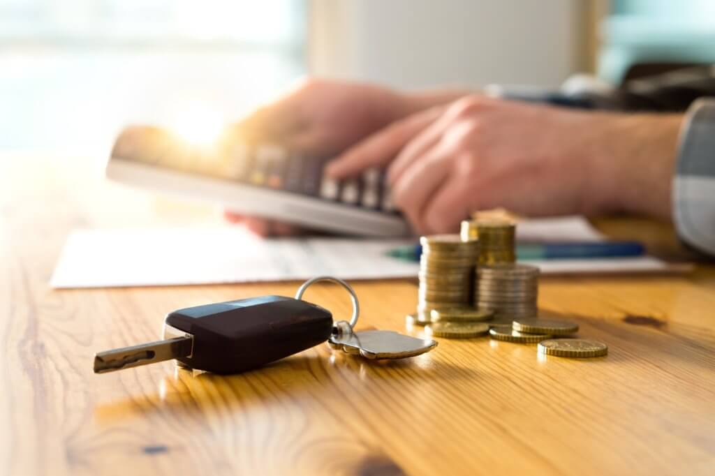 A man using a calculator, with car keys and coins in the foreground