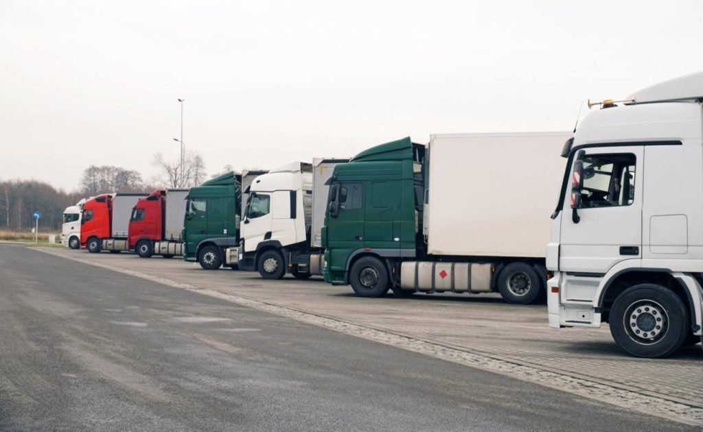 A lineup of semi-trucks next to an asphalt road, with leafless trees in the background