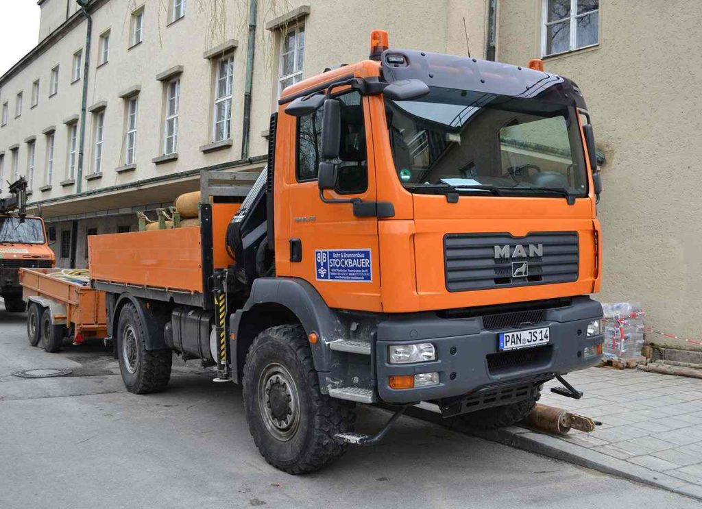 A MAN TGM truck parked on the side of a road at a construction site