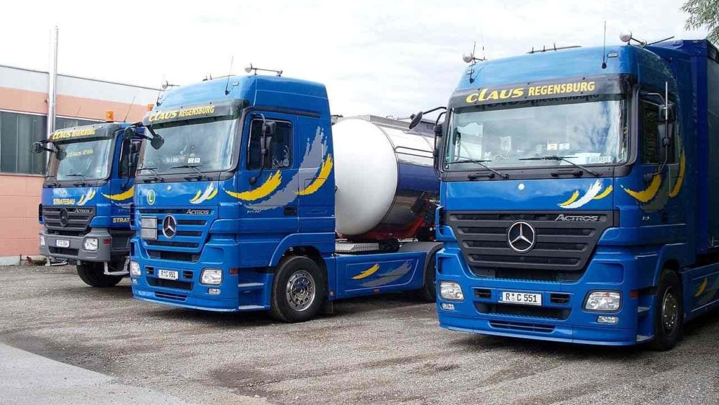 A lineup of three Mercedes trucks parked on gravel