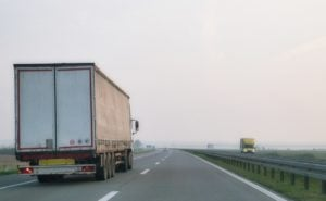 A truck with curtain side trailer driving down a highway on a misty morning