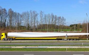 truck carrying long oversized load of wind turbine