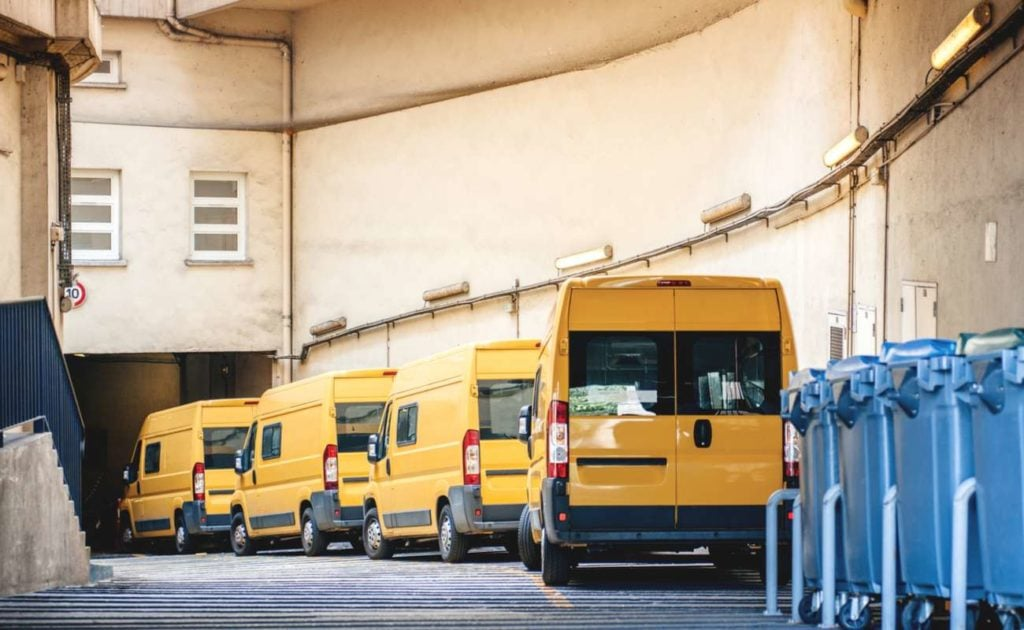 Row of yellow business delivery vans parked