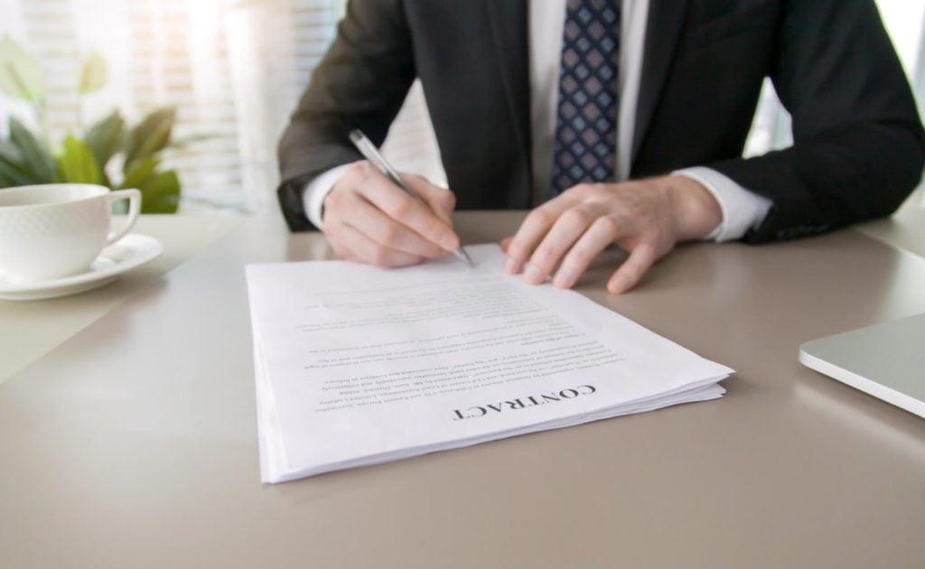 A man in a smart suit signing a contract