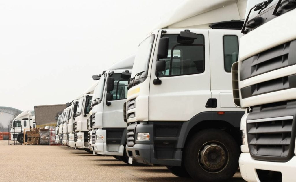 Front of white large trucks parked in a row