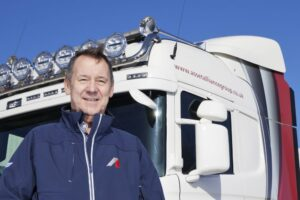 Brian Kempson, Truck and Trailer Sales Director stands infront of a branded Asset Alliance Grouptruck